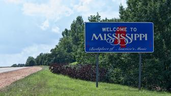 State line sign welcoming travellers to Mississippi.  Copy space over road to the left of the sign.