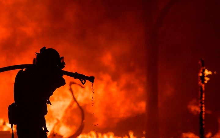 A firefighter pulls a hose in front of a burning house in the Napa wine region of California on Oct. 9, 2017.