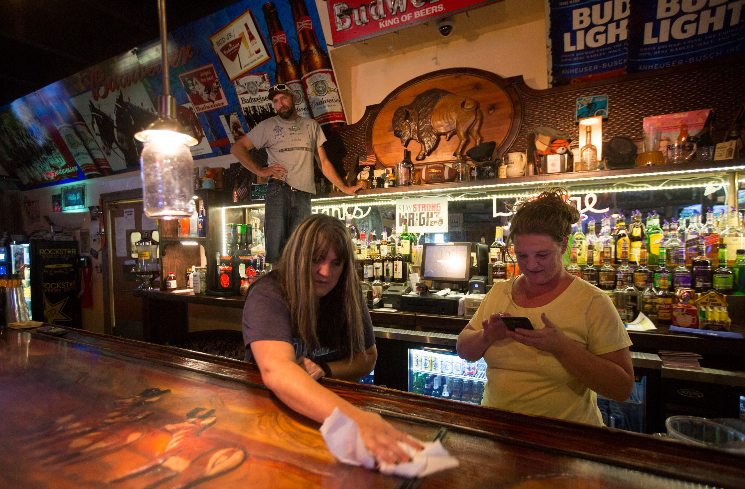 "Lori Sanders, a bartender at Hank's Roadside Bar and Grill in Wright, wipes down the bar. ""We don't put"