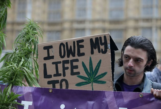 A supporter holding a placard promoting the use of cannabis as a