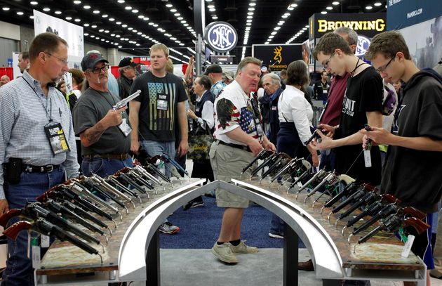 Gun enthusiasts look over Benelli USA guns at a National Rifle Association show in Louisville, Kentucky,...