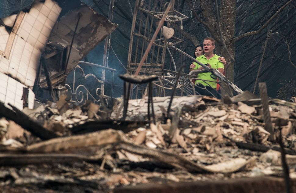 Mark Williams, right, and friend Norina Wong, left, look over the destruction in their friends' neighborhood off Fountaingrov