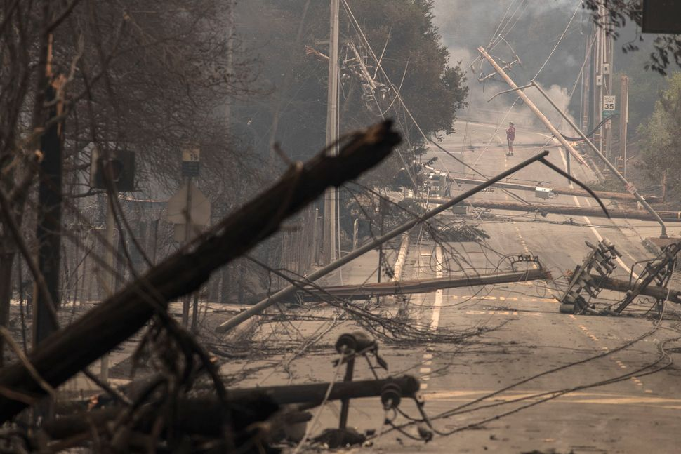 Power poles and lines block a street at Brookdale and Aaron Drive in Hidden Valley, where most of the homes were destroyed by