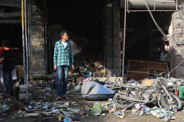 A Syrian resident looks at the damage following a reported airstrike on a vegetable market in Maaret...