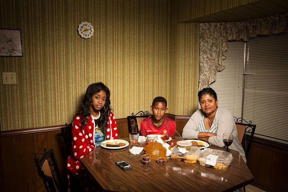 Seynabou, Rui James and Marie eat dinner in Louisiana.