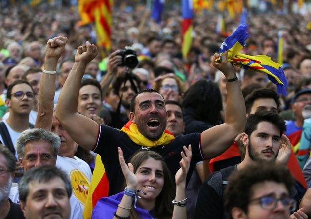 People react towards a giant screen showing events inside the Catalan regional parliament during a pro-indpendence...