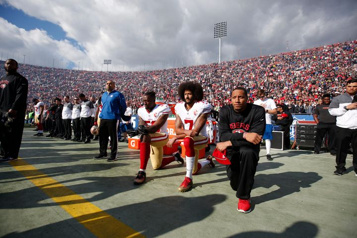 Colin Kaepernick (middle) and two teammates kneel during the national anthem last December before a football game in Los Ange