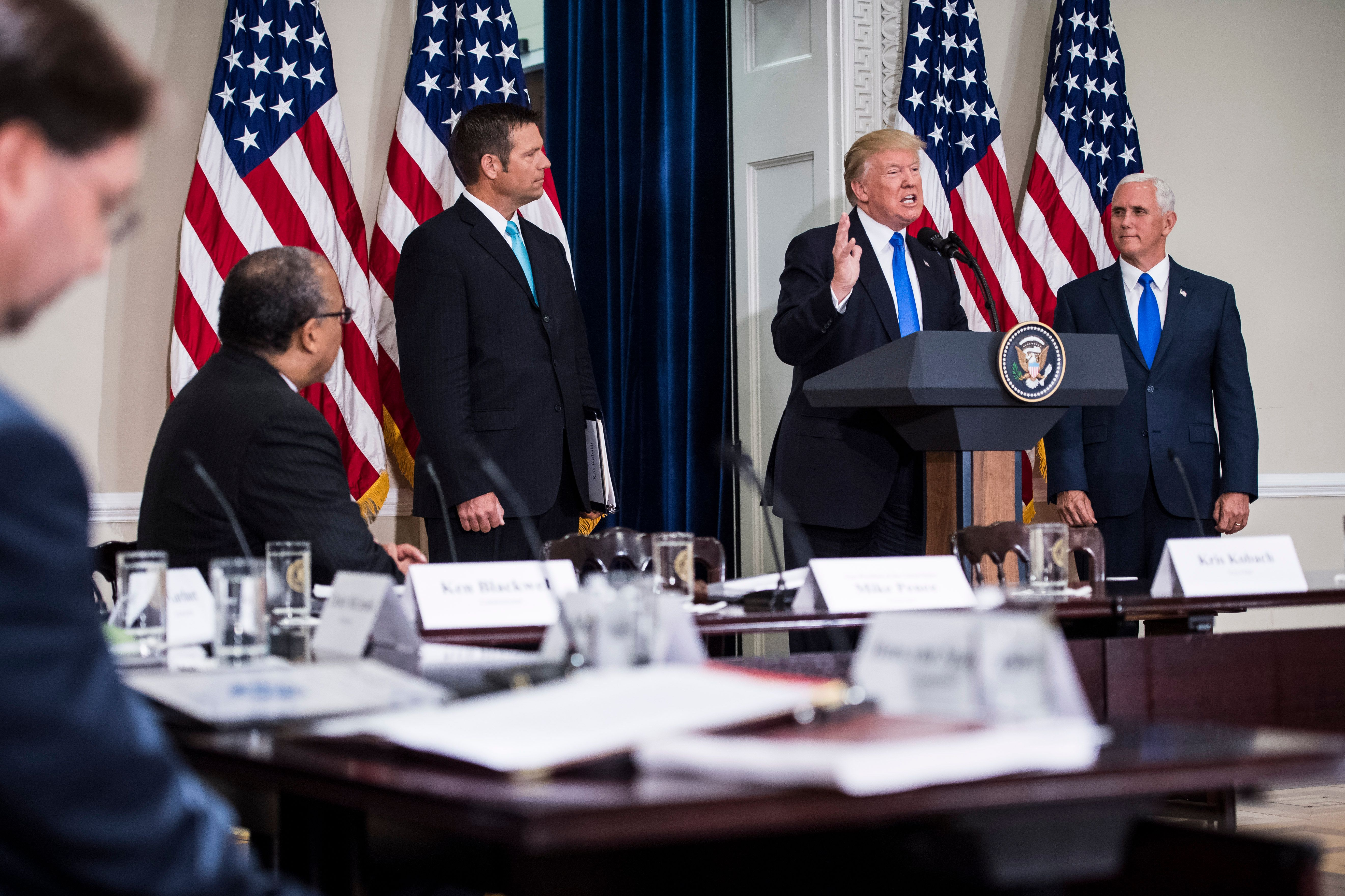 WASHINGTON, DC - JULY 19: President Donald Trump, accompanied by Vice President Mike Pence, right, and Kansas Secretary of State Kris Kobach, center left, speaks at the first meeting of the Presidential Advisory Commission on Election Integrity at the Eisenhower Executive Office Building on the White House complex in Washington, DC on Wednesday, July 19, 2017. (Photo by Jabin Botsford/The Washington Post via Getty Images)