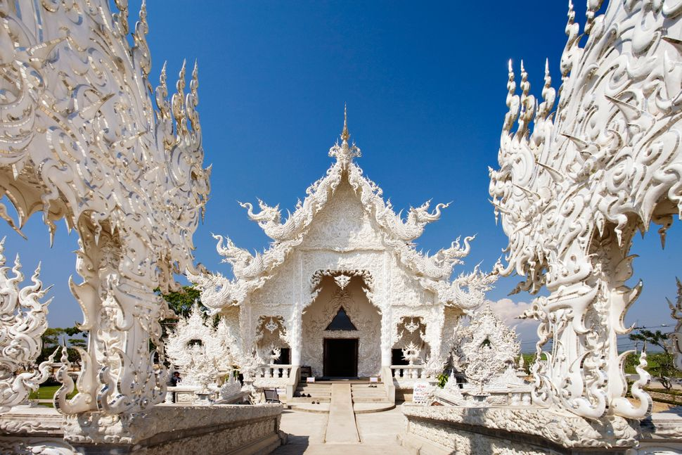 Thailand's Wat Rong Khun, or White Temple, attracts thousands of tourists every year with its intricate carvings depicting <a
