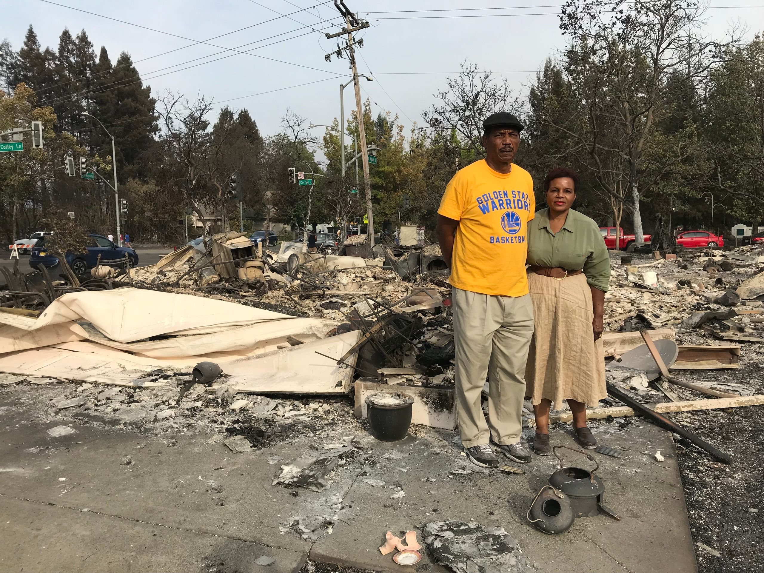 Marion Heim, right, and husband Lloid Heim stand on the ashes where their house used to be, in the days after the fire -- Oct