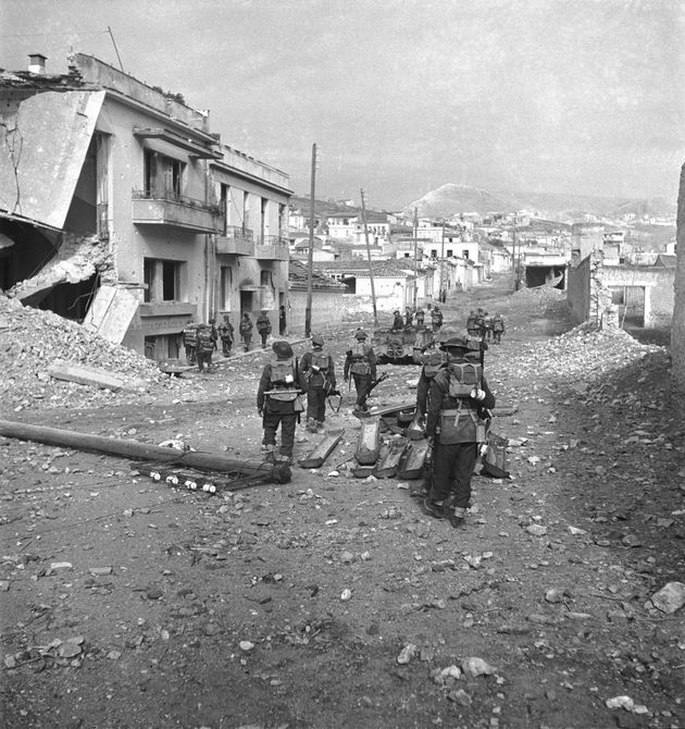 British troops clear the streets among bomb-damaged buildings during the last stages of fighting in