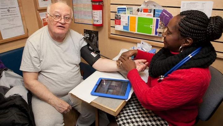 Rainelle Walker-White, assistant director of the Family Van in Boston, takes a patient's blood pressure aboard the mobile hea