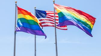 Two Rainbow Flags and a American Flag flying