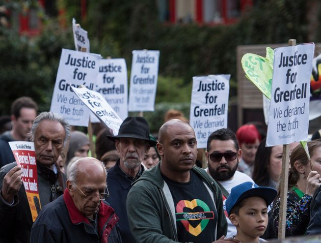 People take part in a silent march for Grenfell Tower fire victims in west