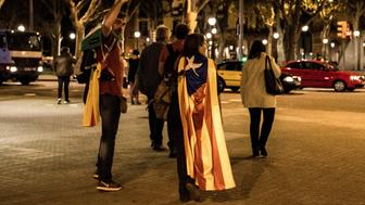 BARCELONA, CATALONIA, SPAIN - 2017/10/10: People seen gathering to follow the speech of the Catalan President Carles Puigdemont while wearing a catalonia flag in the regional Parliament, in downtown Barcelona Catalan independence campaign. 30,000 people have been able to follow by large screens located outside the Parliament for the Declaration of independence of Catalonia declared by Carles Puigdemon . But the joy of the present has lasted only for few seconds when President Puigdemon declared at the same time the suspension of this Declaration to begin a dialogue with the Spanish Government. (Photo by Brais G Rouco/SOPA Images/LightRocket via Getty Images)