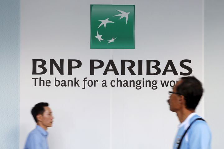 People pass a BNP Paribas bank logo in Singapore's central business district in a photo shot in January 2016.