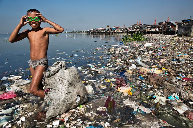 Rodello Coronel, age 13, picks through trash on the beach for recyclable plastic he can sell to support his family in Manilla