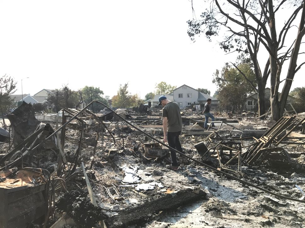 Maryanne Rahab (right) walks through the rubble of the house she had been renting in Coffey Park for over a year with he