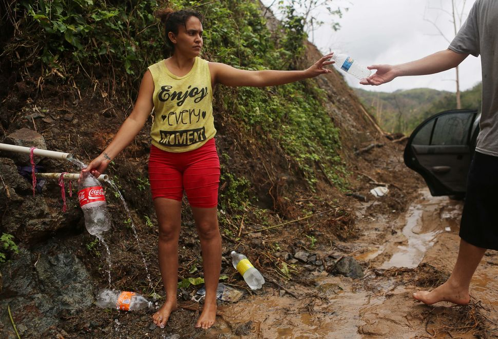 Puerto Rican resident Yanira Rios collects spring water nearly three weeks after Hurricane Maria destroyed her town of Utuado