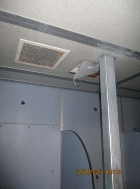 An electric wire hangs above a shower at HMP