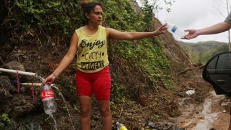 UTUADO, PUERTO RICO - OCTOBER 10:  Yanira Rios collects spring water for her house nearly three weeks after Hurricane Maria hit the island, on October 10, 2017 in Utuado, Puerto Rico. Her house and most of the municipality is without running water or grid power. Only 16 percent of Puerto Rico's grid electricity has been restored. Puerto Rico experienced widespread damage including most of the electrical, gas and water grid as well as agriculture after Hurricane Maria, a category 4 hurricane, swept through.  (Photo by Mario Tama/Getty Images)