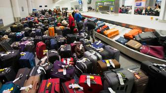 TORONTO, ON:TORONTO, ON:TORONTO, ON - JANUARY 7: Travellers scour the baggage claim at Toronto's Pearson airport for their luggage. Cold weather has caused a series of delayed or cancelled flights.        (Randy Risling/Toronto Star via Getty Images)