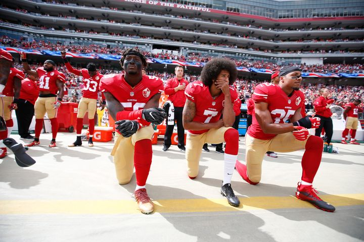 Antoine Bethea and Rashard Robinson raise their fists during the national anthem as Eli Harold, left, Colin Kaepernick and Eric Reid take a knee prior to a game against the Dallas Cowboys on Oct. 2, 2016.
