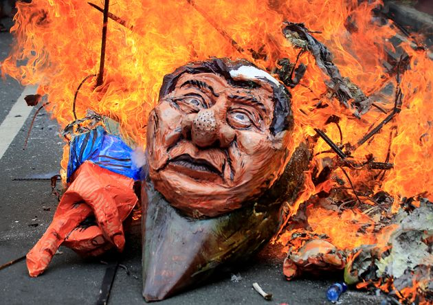 Protesters burn an effigy of Philippine President Rodrigo Duterte to express their outrage while calling...