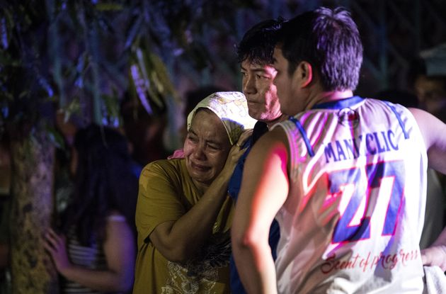Relatives of Aldrin Castillo, an alleged drug user killed by unidentified assailants, grieve as they...