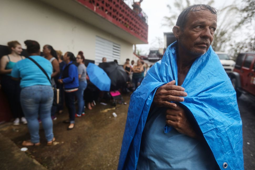 Arian Rodriguez covers himself in a tarp as residents of Juyuya wait in the rain for more than seven hours to register with F