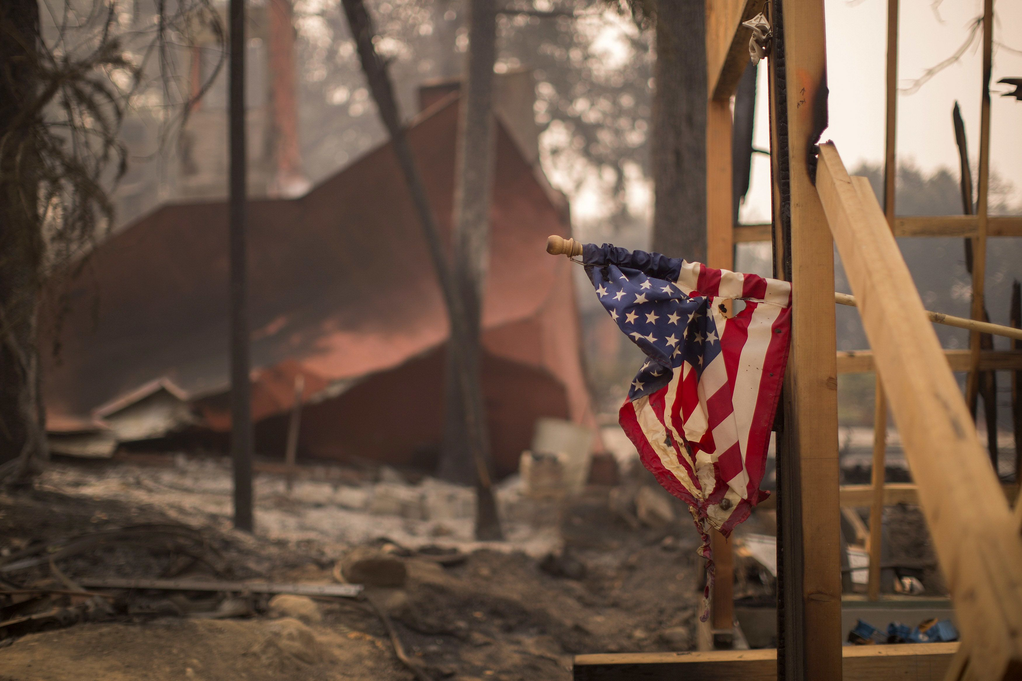 NAPA, CA -OCTOBER 11: A construction site American flag hangs partly melted among houses in Soda Canyon that were destroyed by the Atlas Fire on October 11, 2017 near Napa, California. In one of the worst wildfires in state history, more than 2,000 homes have burned and  at least 21 people were killed as more than 14 wildfires continue to spread with little containment in eight Northern California counties.   (Photo by David McNew/Getty Images)