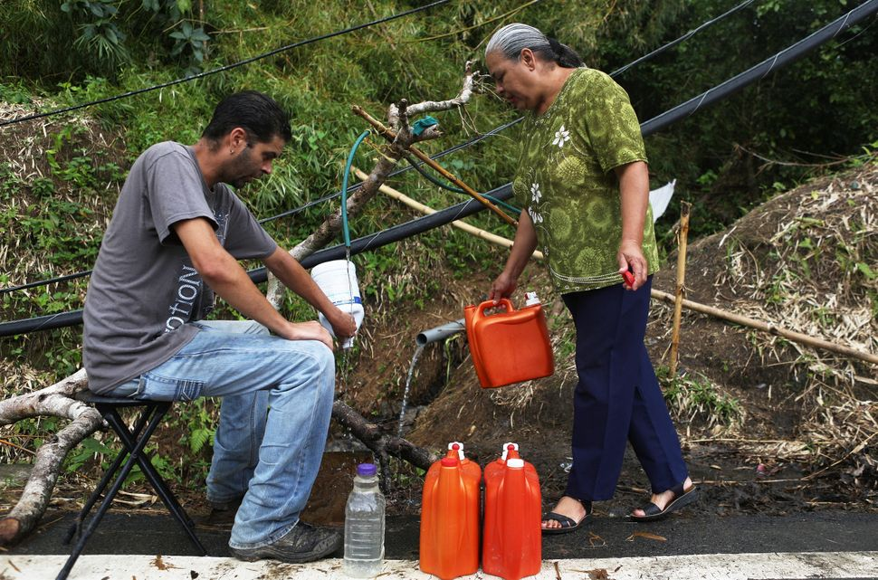 Migdalia Aceuedo and her son collect spring water in Utuado near a downed power line. Their house and much of the town is wit