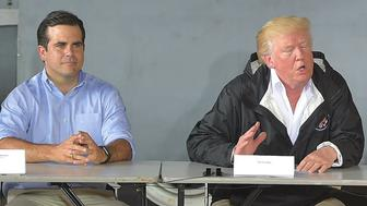 US President Donald Trump and First Lady Melania Trump attend a meeting with Governor Ricardo Rossello (L)and other officials after stepping off Air Force One upon arrival at Luis Muñiz Air National Guard Base in Carolina, Puerto Rico on October 3, 2017. Nearly two weeks after Hurricane Maria thrashed through the US territory, much of the islands remains short of food and without access to power or drinking water. / AFP PHOTO / MANDEL NGAN        (Photo credit should read MANDEL NGAN/AFP/Getty Images)