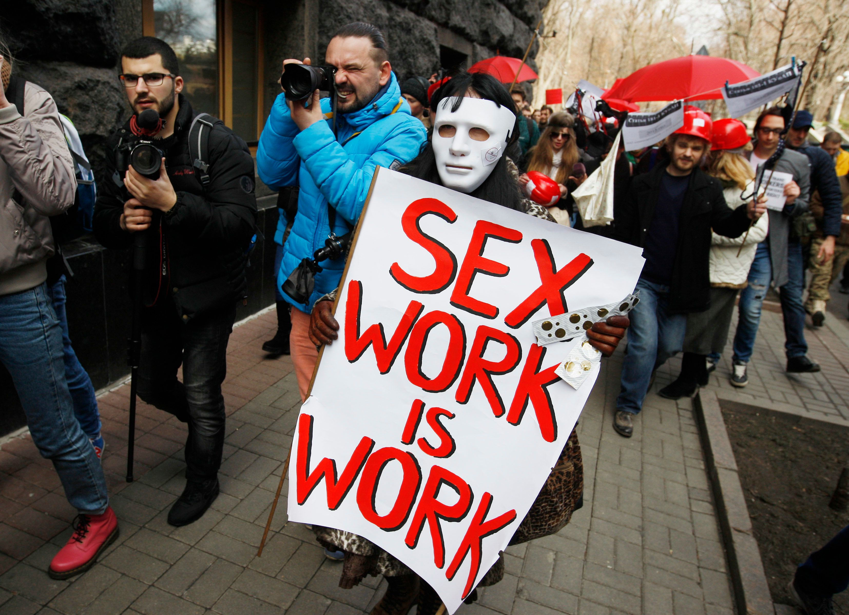 "The sex workers and human right activists, wearing white masks and hold placards,as they attend ""The march of the sex workers"", demanding to cancel an administrative penalty for prostitution, and to pay attention to the observance of the human rights of sex workers,during their protest near Ukrainian Parliament,the Cabinet of Ministers,and the President Administration, in Kiev, Ukraine, 03 March,2017.  (Photo by STR/NurPhoto via Getty Images)"
