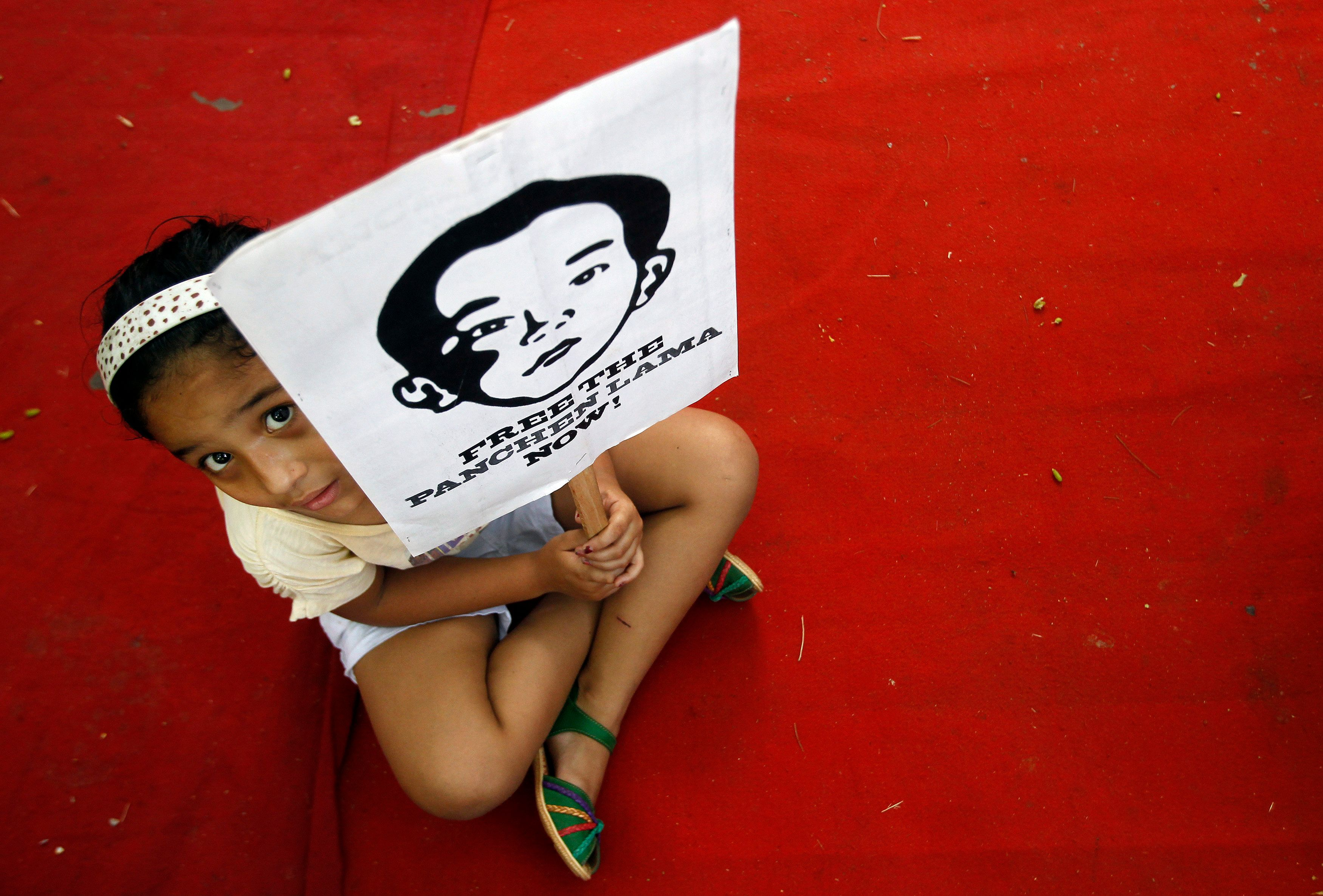 A Tibetan girl holds a placard featuring Gedhun Choekyi Nyima, the 11th Panchen Lama, during a protest ahead of Chinese Premier Li Keqiang's visit to India, in New Delhi May 17, 2013. Dozens of Tibetans on Friday held a protest demanding the release of Gedhun Choekyi Nyima who, according to the protesters, is in detention in China. Li is scheduled to arrive in New Delhi on May 19. REUTERS/Anindito Mukherjee (INDIA - Tags: POLITICS CIVIL UNREST)