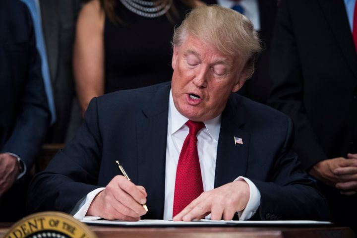 President Donald Trump signs an executive order on health care in the Roosevelt Room at the White House in Washington, DC on