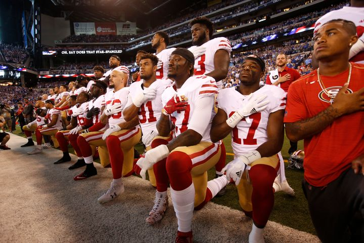 The San Francisco 49ers kneel and stand together while the national anthem plays prior to their game against the In