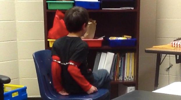 An image from a viral video of a child being handcuffed by a school resource officer