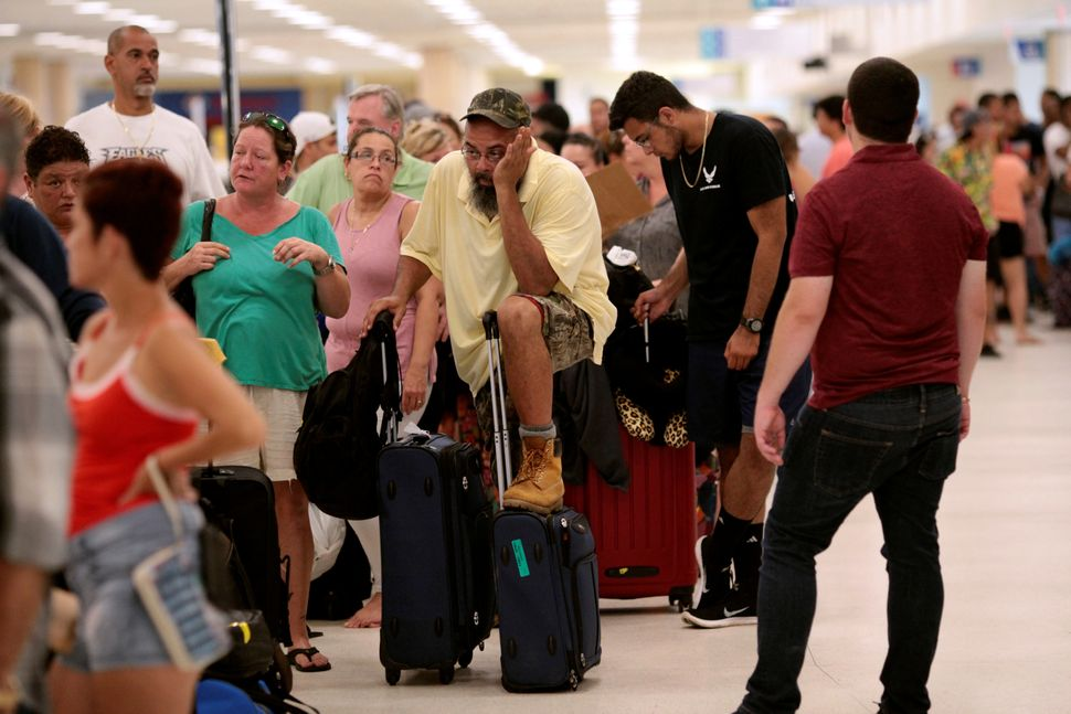Stranded tourists and Puerto Ricans line up at the International Airport in San Juan on Sept. 25 as they try to leave after H