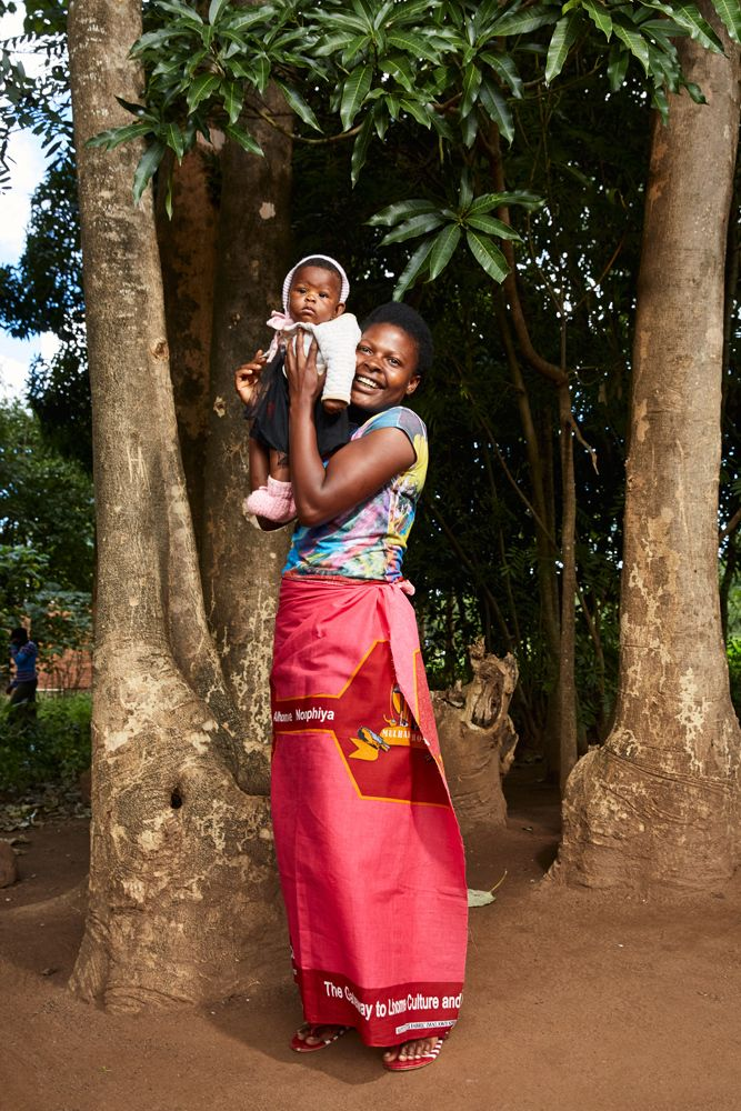 Jennifer, a Green Malata student, holds up another church member's child as she poses outside the Well Of Life Church after a