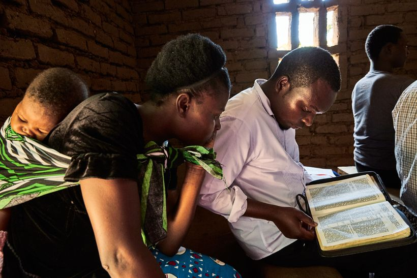 Jennifer and Wyclef read along with a sermon during a Sunday morning service at the Well of Life Church in Luchenza, southern