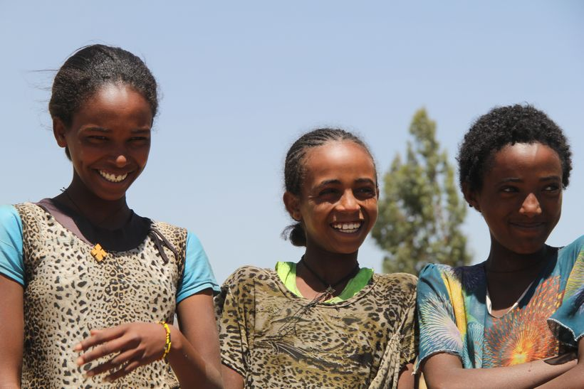 Nigisti and two of her friends smile as they watch their schoolmates wash their hands.