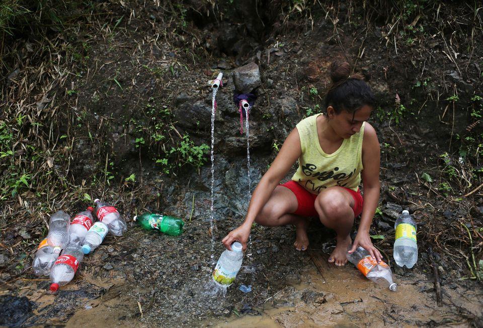 Yanira Rios recoge agua de un manantial para usarla en su casa en Utuado, Puerto Rico. La mayor parte...
