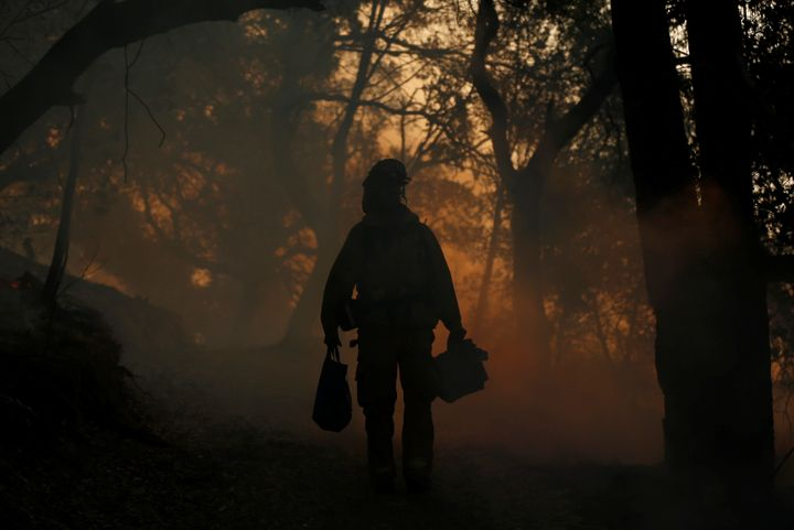 A firefighter brings supplies to crewmates, while working to control a wildfire in Sonoma, California, U.S., October 14, 2017