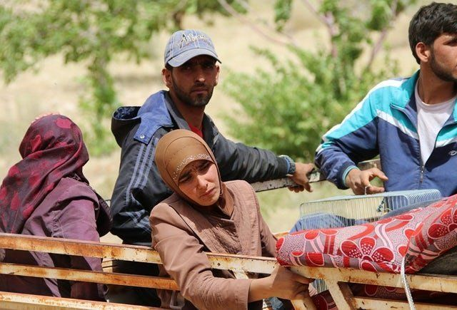 Syrian refugees are seen on the back of a pickup truck in the Lebanese eastern border town of Arsal as they head toward the S