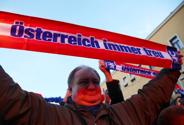 """A supporter holds a banner reading """"Austria always loyal"""" during the Austrian Freedom Party's final election campaign rally i"""