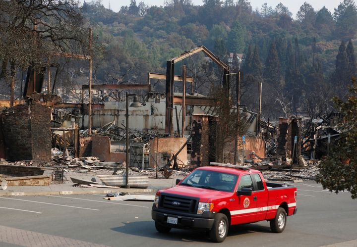 A firefighting crew drives pass a business destroyed in wildfire that tore through Santa Rosa, California, U.S., October 15,