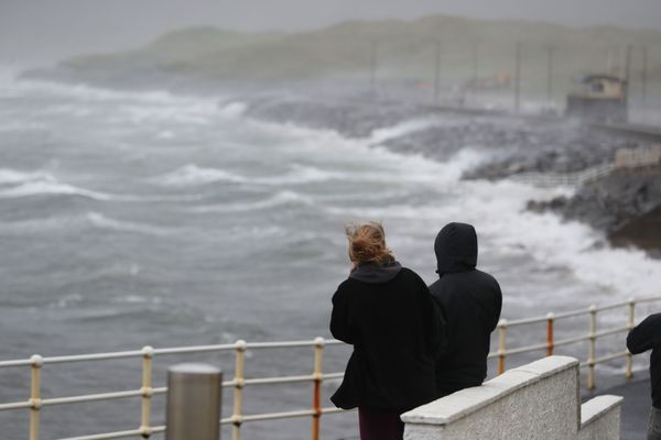 People watch the waves and sea spray at Lahinch in County Clare on the West Coast of Ireland.