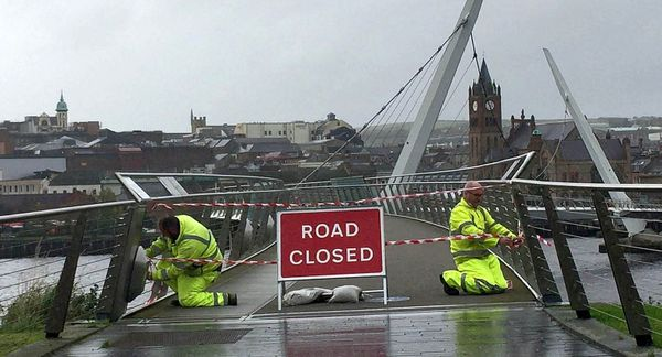 Staff from the Northern Ireland Road Service close the Peace Bridge in Londonderry, as Hurricane Ophelia hits the UK and Irel