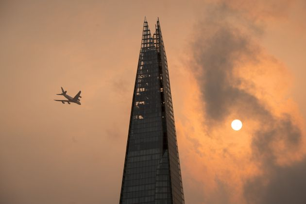 A plane flies past the Shard in central London, as the sky takes on an unusual orange colour caused by...